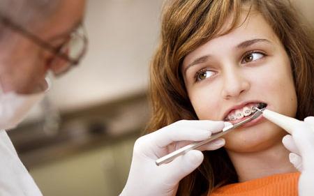 Фото: установка брекетов врачом ортодонтом